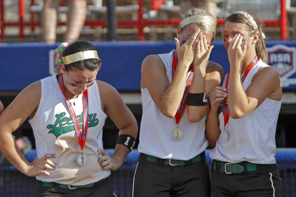 Photo - Leedey softball team members Taya Haney, Sydney Harrel and Jenna Trissel, from left, react after their 8-6 loss to Red Oak during the Class A state championship softball tournament at ASA Hall of Fame Stadium on Wednesday, May 2, 2012, in Oklahoma City, Oklahoma. Photo by Chris Landsberger, The Oklahoman