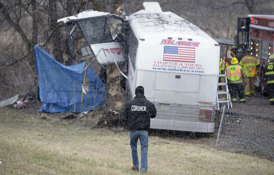 Photo - Members of the Cumberland County Coroners Office investigate the scene of a tour bus crash on the Pennsylvania Turnpike on Saturday, March 16, 2013 near Carlisle, Pa.  Authorities say the tour bus crashed on the freeway at mile marker 227 in central Pennsylvania, and serious injuries have been reported.  Lacrosse players from Seton Hill University and three coaches were among the 23 people aboard when the bus crashed at about 9 a.m., turnpike spokeswoman Renee Colborn said. It's not clear what caused the crash, but state police were investigating, said Megan Silverstram of the Cumberland County public safety department. (AP Photo/The Sentinel, Jason Malmont ) MANDATORY CREDIT