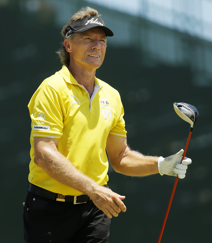 Photo - Bernhard Langer watches his tee shot on No. 18 during practice rounds for the U.S. Senior Open golf tournament at Oak Tree National in Edmond, Okla., Wednesday, July 9, 2014. Photo by Nate Billings, The Oklahoman