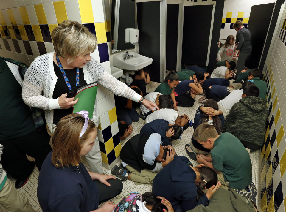 """Photo - Arthur Elementary third-graders assume their """"duck and cover"""" posture as teacher Cheri Reilly directs them in storm preparation assembly areas on Tuesday, April 1, 2014 in Oklahoma City, Okla.  Photo by Steve Sisney, The Oklahoman"""