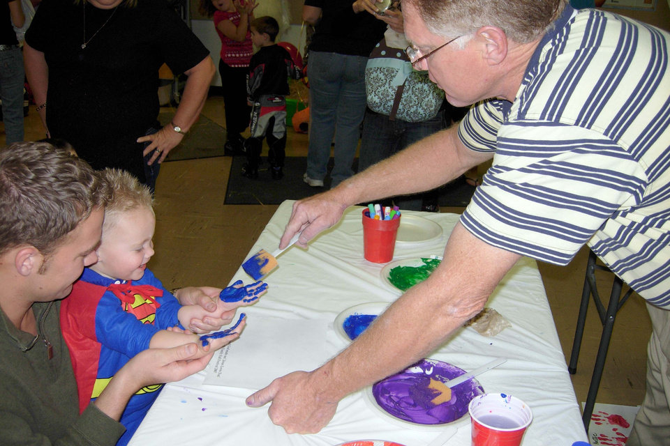 Charlie Stowe helps a Family Fall Festival participant get ready to do handprints at the Arts and Crafts booth at the Family Fall Festival and Trunk or Treat event at First Christian Church in Guthrie on Sunday, Oct. 28.<br/><b>Community Photo By:</b> Karen Allen<br/><b>Submitted By:</b> Karen,
