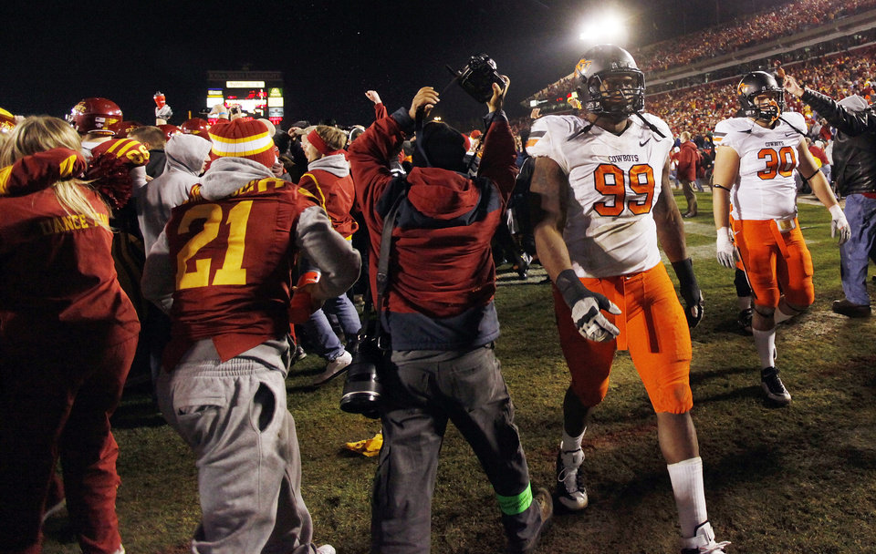 Photo - ISU fans rush the field past OSU's Richetti Jones (99) and David Paulsen (30) after a college football game between the Oklahoma State University Cowboys (OSU) and the Iowa State University Cyclones (ISU) at Jack Trice Stadium in Ames, Iowa, Friday, Nov. 18, 2011. Iowa State won, 37-31, in double overtime. Photo by Nate Billings, The Oklahoman