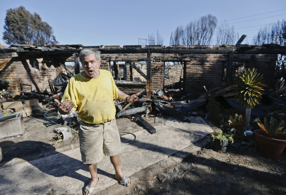 Photo - Greg Saska stands outside his home that was destroyed by wildfire as he talks about his loss, Thursday, May 15, 2014, in Carlsbad, Calif. Nine fires in all were burning an area of more than 14 square miles (36 square kilometers) amid a heat wave and dry conditions, said San Diego County officials, who warned also of poor air quality with black and gray smoke wafting over the region. The wildfires drove tens of thousands from their homes and shut down schools and amusement parks, including Legoland.  (AP Photo/Lenny Ignelzi)
