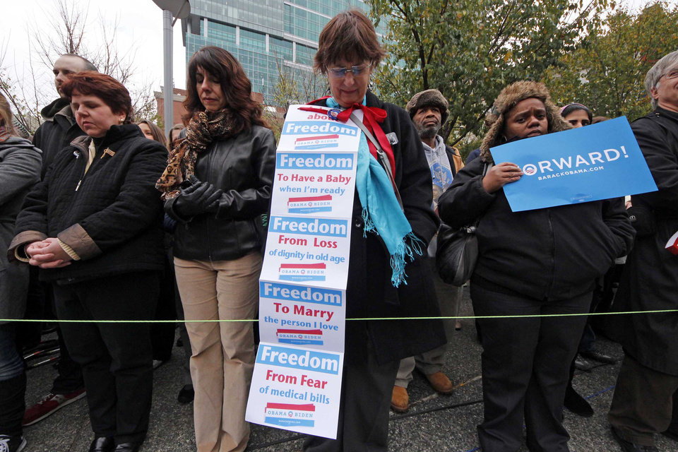 Photo -   Linda Everhart of Pittsburgh, center, joins others gathered to hear former President Bill Clinton speak at a rally to get out the vote for President Barack Obama, in a prayer in downtown Pittsburgh, Monday, Nov. 5, 2012. (AP Photo/Gene J. Puskar)