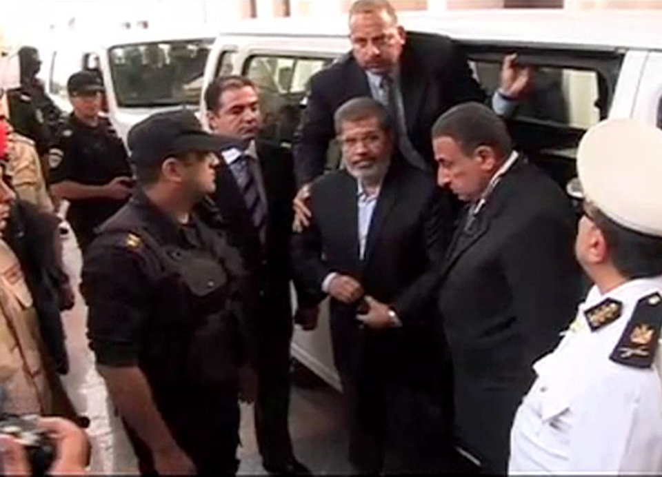 Photo - FILE - In this Monday, Nov. 3, 2013 file image made from video provided by Egypt's Interior Ministry shows ousted President Mohammed Morsi,center, arrives for a trial hearing in Cairo, Egypt. In sharp contrast to his first court appearance when he wore a trim dark suit and spoke authoritatively, Egypt's toppled President Mohammed Morsi stood alone in a soundproof glass-encased metal cage Tuesday, Jan. 28, 2014, used for the first time in this country, in a white prison uniform.(AP Photo/Egyptian Interior Ministry, File)