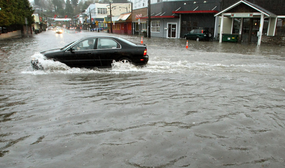 Photo -   A car attempts to navigate through the deep water on Bay Street in Port Orchard, Wash., on Monday. Nov. 19, 2012. Heavy rains inundated the areas storm drains and caused flooding in the Port Orchard, Wash., downtown district and elsewhere in Kitsap County. (AP Photo/Kitsap Sun, Meegan M. Reid)