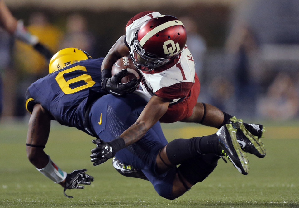Photo - Oklahoma's K.J. Young (1) is tackled by West Virginia's Dravon Henry (6)  during the college football game between West Virginia  Mountaineers and the University of Oklahoma Sooners at Milan Puskar Stadium in Morgantown, W.Va., Saturday, Sept. 20, 2014. Photo by Sarah Phipps, The Oklahoman
