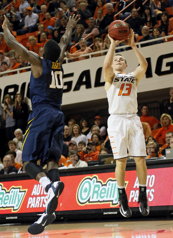 Photo - Oklahoma State's Phil Forte (13) takes a 3-point shot over West Virginia's Eron Harris (10) during an NCAA men's basketball game between Oklahoma State University (OSU) and West Virginia at Gallagher-Iba Arena in Stillwater, Okla., Saturday, Jan. 26, 2013. Oklahoma State won, 80-66. Photo by Nate Billings, The Oklahoman