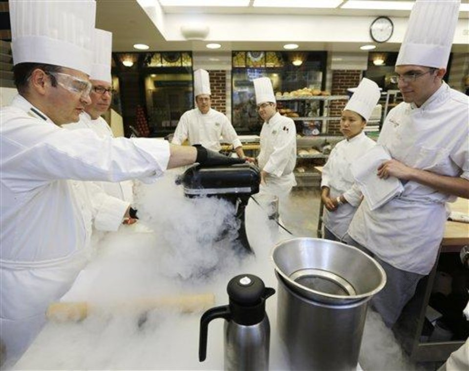 Photo - In this image taken on Friday, Sept. 14, 2012, Chef Francisco Migoya, left, demonstrates how to make strawberry sorbet by applying liquid nitrogen to a puree mixture at the Culinary Institute of America in Hyde Park, N.Y. This esteemed cooking school north of New York City is dramatically pumping up science instruction, saying that tomorrow's chefs will need more technical know-how in the age of molecular gastronomy and sous-vide. (AP Photo/Mike Groll)