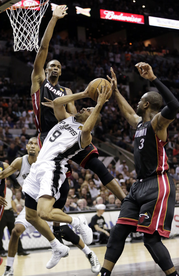 Photo - San Antonio Spurs' Tony Parker (9) attempts to shoot as Miami Heat's Chris Bosh (1) and Dwyane Wade (3) defend during the first half at Game 4 of the NBA Finals basketball series, Thursday, June 13, 2013, in San Antonio. (AP Photo/Eric Gay)