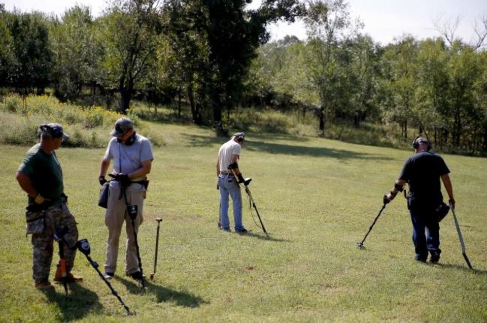 Photo -  Metal detector enthusiasts walk across a field in Fallis. [Bryan Terry/The Oklahoman]