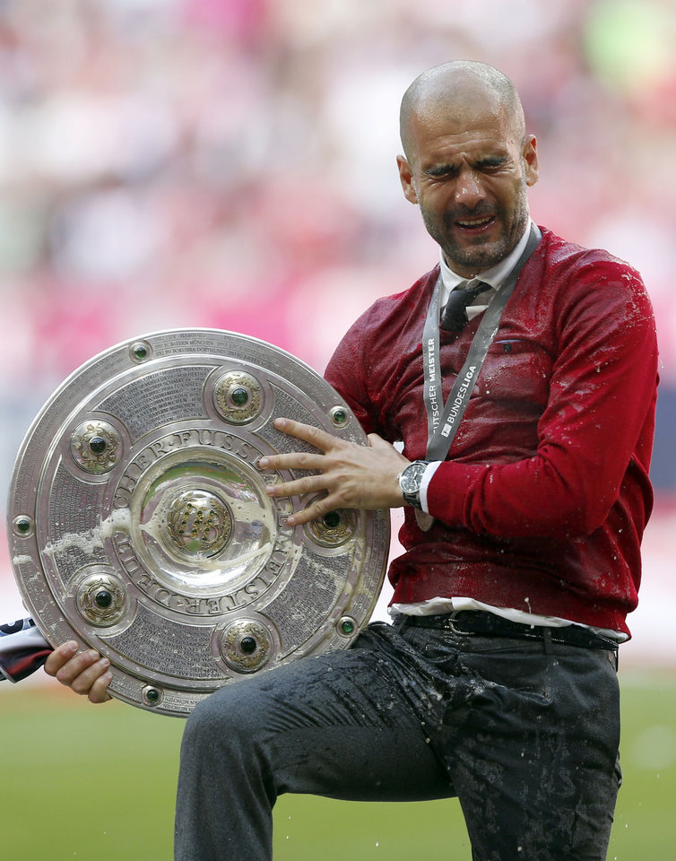 Photo - Bayern head coach Pep Guardiola of Spain was showered with beer after winning the German Soccer Championship after the season's last home game between FC Bayern Munich and VfB Stuttgart, in Munich, southern Germany, Saturday, May 10, 2014. (AP Photo/Matthias Schrader)