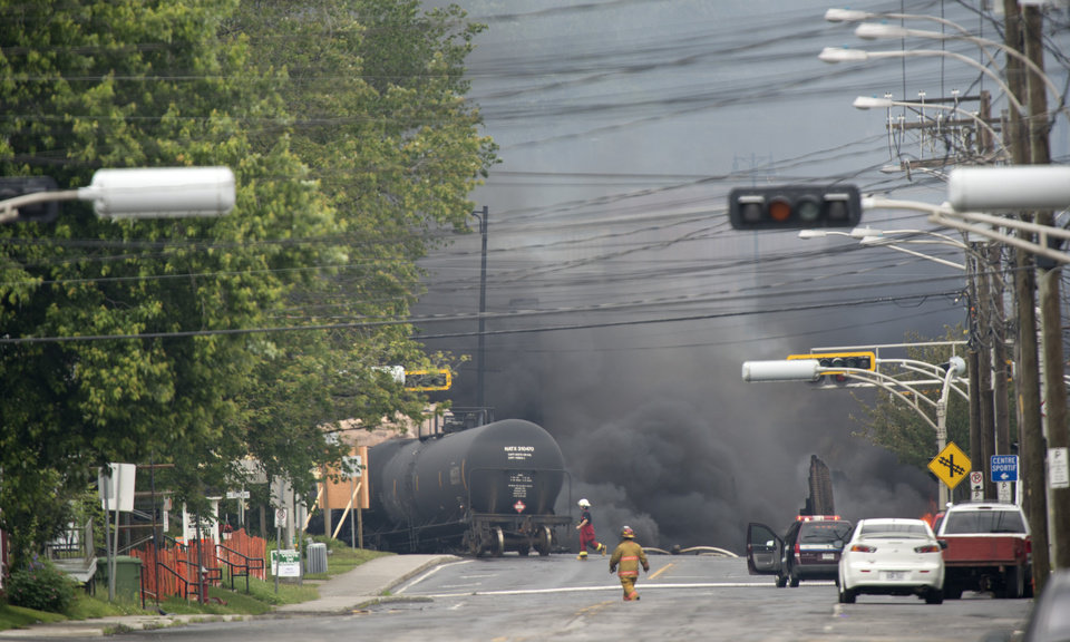 Photo - Smoke rises from railway cars that were carrying crude oil after derailing in downtown Lac Megantic, Quebec, Canada, Saturday, July 6, 2013. The derailment sparked several explosions and forced the evacuation of up to 1,000 people. (AP Photo/The Canadian Press, Paul Chiasson)