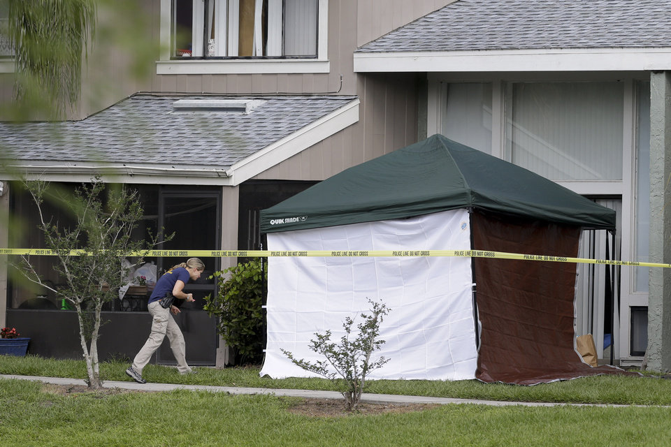 Photo - An FBI investigator walks to the apartment where a man was shot by an FBI agent, Wednesday, May 22, 2013, in Orlando, Fla. The FBI says the man, being questioned by authorities in the Boston bombing probe, was fatally shot when he initiated a violent confrontation. (AP Photo/John Raoux)