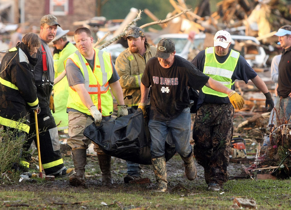Photo - A group of unidentified emergency volunteers move a body recovered among the devastation in Smithville, Mississippi after a tornado destroyed much of the small town on Wednesday, April 27, 2011.(AP Photo/The Northeast Mississippi Daily Journal, C. Todd Sherman)