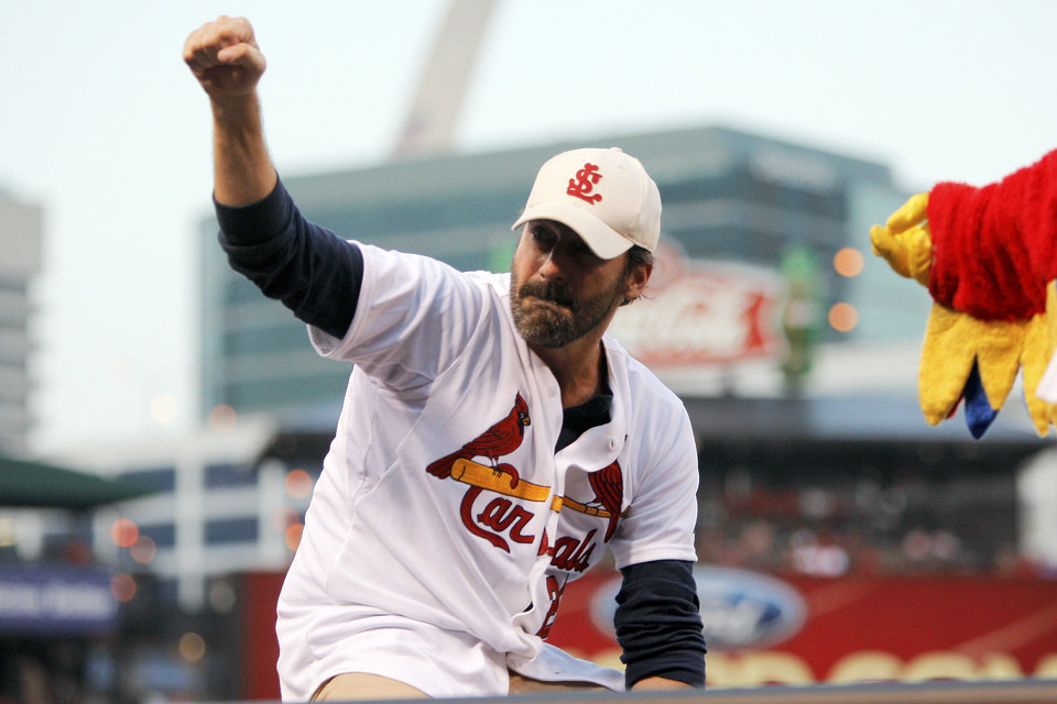 Photo - Actor and St. Louis native Jon Hamm acknowledges fans prior to throwing out a ceremonial first pitch before a baseball game between the St. Louis Cardinals and the Cincinnati Reds, Monday, Aug. 18, 2014, in St. Louis. Hamm is being honored tonight by the Cardinals with a give-away promotion, and portions of proceeds from the purchase of promotional tickets being donated to St. Jude Children's Medical Research Hospital in his honor. (AP Photo/Scott Kane)