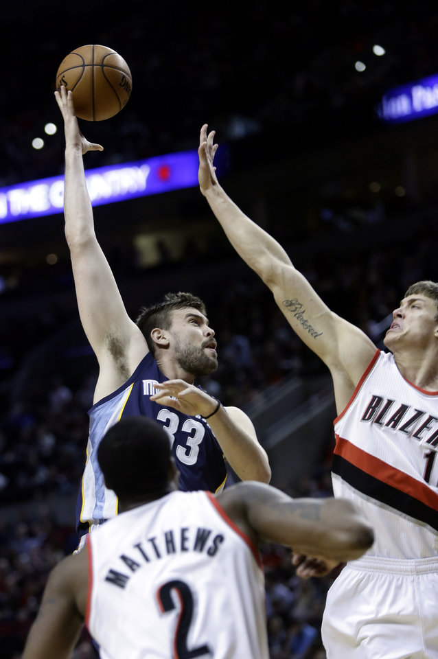 Memphis Grizzlies center Marc Gasol, left, from Spain, shoots over Portland Trail Blazers center Meyers Leonard, right, and Wesley Matthews during the first quarter of an NBA basketball game in Portland, Ore., Wednesday, April 3, 2013.(AP Photo/Don Ryan)
