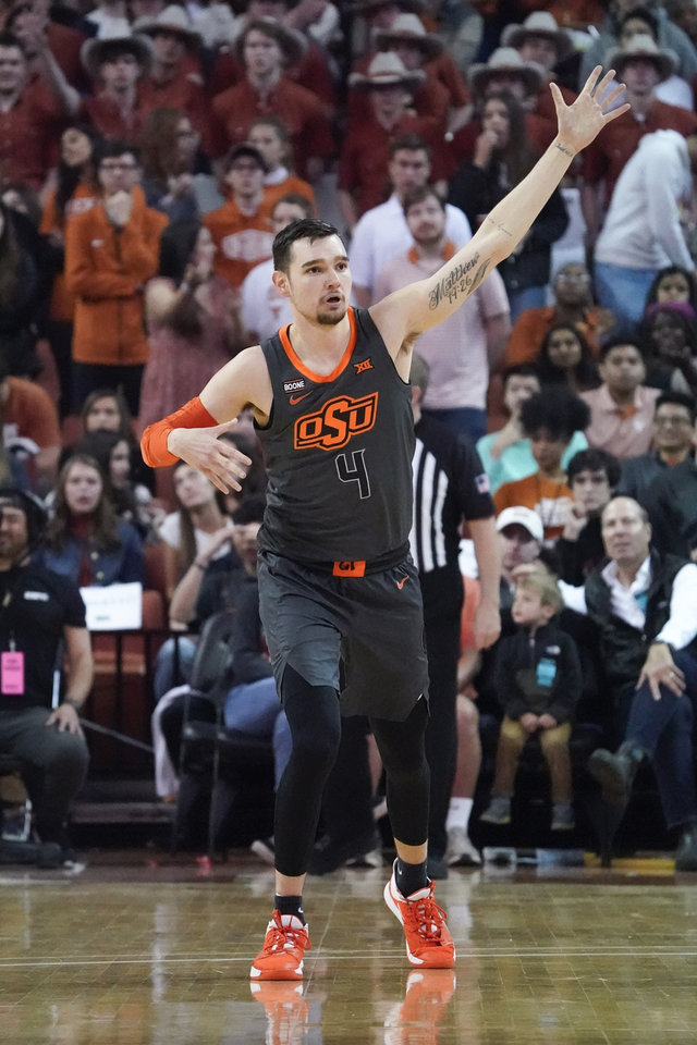 Photo - Mar 7, 2020; Austin, Texas, USA; Oklahoma State Cowboys guard Thomas Dziagwa (4)  pretends to shoot a bow and arrow after scoring in the first half against the Texas Longhorns at Frank C. Erwin Jr. Center. Mandatory Credit: Scott Wachter-USA TODAY Sports