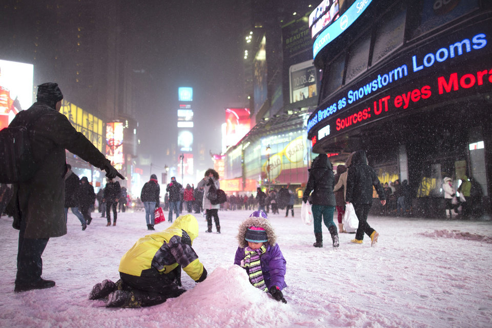Photo - Children make a snow pile in Times Square, during a snowstorm, Thursday, Jan. 2, 2014, in New York. The storm is expected to bring snow, stiff winds and punishing cold into the Northeast. (AP Photo/John Minchillo)