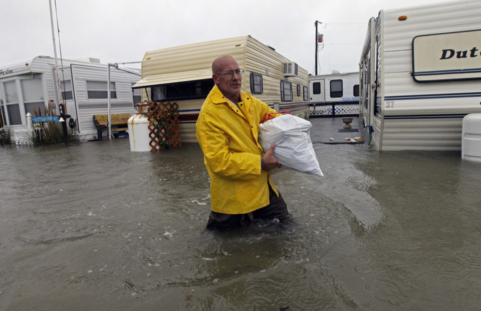 Terry Robinson wades through water after retrieving some of his belongings from his flooded trailer at RV Park in Kitty Hawk, N.C., Monday, Oct. 29, 2012. Flooding from Hurricane Sandy left many roads impassable while localized flooding from a storm surge forced some people from their homes. (AP Photo/Gerry Broome) ORG XMIT: NCGB104