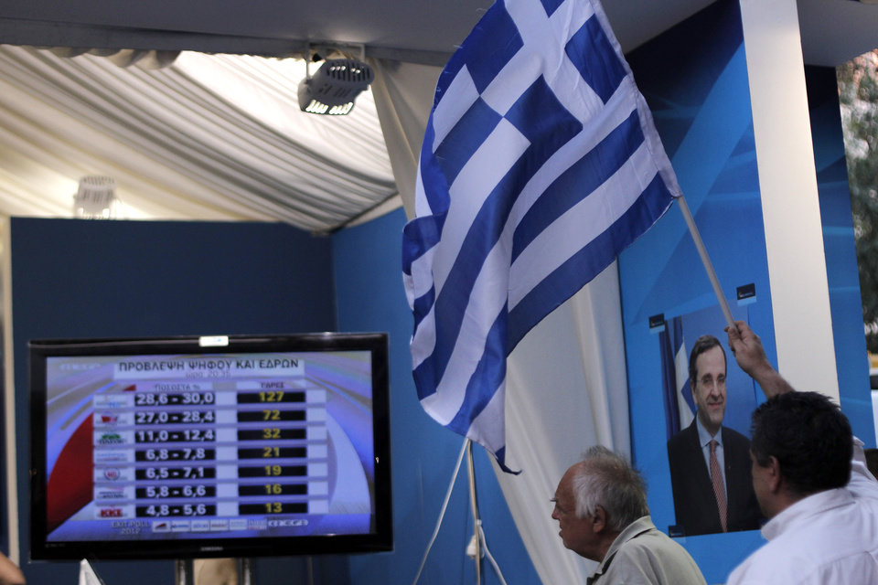 Photo -   New Democracy conservative party supporters wave a Greek flag as a TV screen shows results at an election kiosk at Syntagma square in Athens, Sunday, June 17, 2012. The pro-bailout New Democracy party came in first Sunday in Greece's national election, and its leader has proposed forming a pro-euro coalition government.(AP Photo/Petros Giannakouris)
