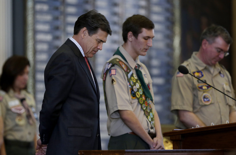 Gov. Rick Perry, left, bows his head for the invocation during the annual Boy Scouts Parade and Report to State in the House Chambers at the Texas State Capitol, Saturday, Feb. 2, 2013, in Austin, Texas. Perry says he hopes the Boy Scouts of America doesn\'t move soften its mandatory no-gays membership policy. (AP Photo/Eric Gay)