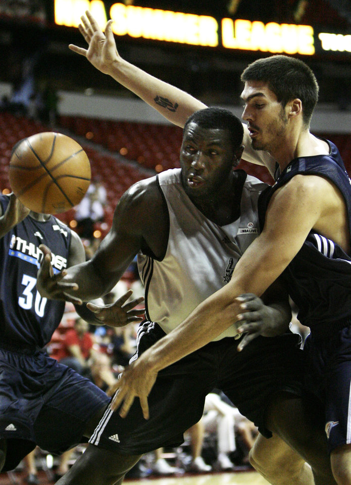 Photo - BYRON MULLENS: San Antonio Spurs' first-round draft pick DeJuan Blair, center, battles for the ball with Oklahoma City Thunder's B.J. Mullens during their NBA Summer League Basketball game at Thomas & Mack Arena in Las Vegas on Thursday, July 16, 2009. (AP Photo/Laura Rauch) ORG XMIT: NVLR103