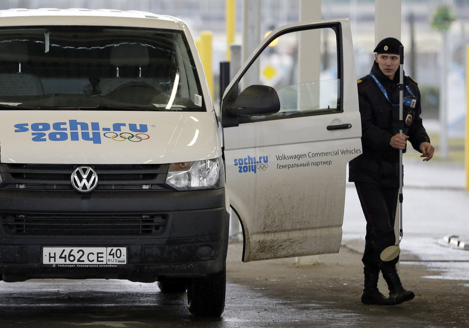 Photo - A Russian police officer searches a vehicle at an entrance to the Sochi 2014 Olympic Winter Games park, Thursday, Jan. 23, 2014, in Sochi, Russia. The Olympics begin on Feb. 7. (AP Photo/David J. Phillip)