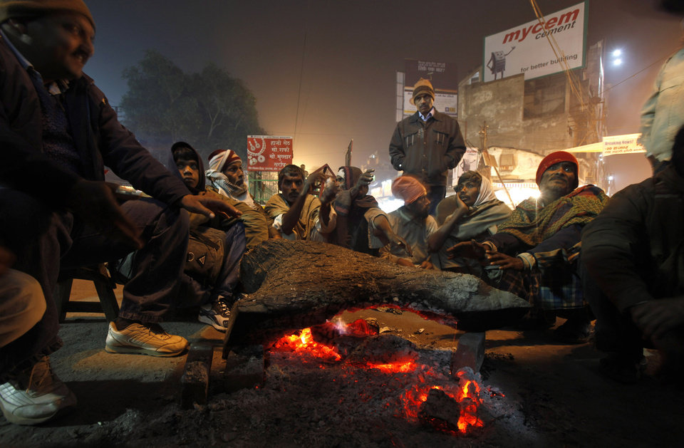 In this Wednesday, Dec. 26, 2012 photo,  passengers stay warm by a fire as they wait for the arrival of a train in Allahabad, India. Thick fog affected flights and trains with some trains reportedly running over 15 hours late. (AP Photo/Rajesh Kumar Singh)