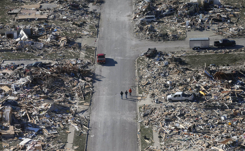Photo - ADVANCE FOR USE SUNDAY, DEC. 22 AND THEREAFTER - FILE - This Monday, Nov. 18, 2013 aerial file photo shows people walking down a street where homes once stood that were destroyed by a tornado that hit the western Illinois town of Washington. Two dozen tornadoes swept through the state killing seven people. It was voted as one of the top 10 stories in Illinois for 2013. (AP Photo/Charles Rex Arbogast, File)