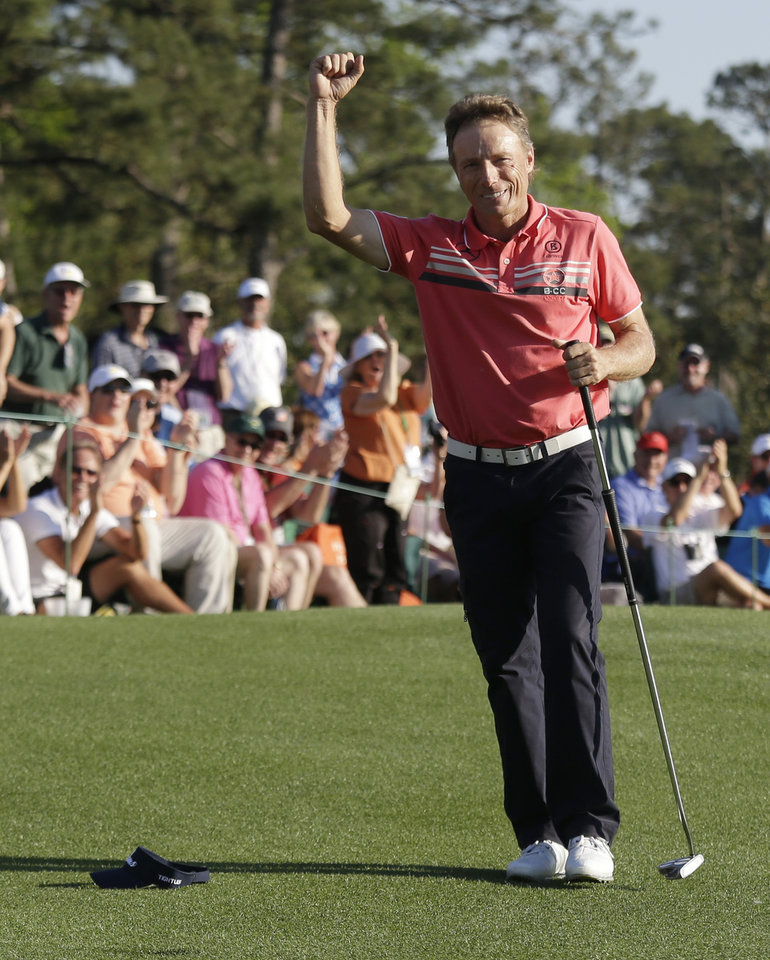 Photo - Bernhard Langer, of Germany, pumps his fist after saving par on the 18th hole during the first round of the Masters golf tournament Thursday, April 10, 2014, in Augusta, Ga. (AP Photo/Darron Cummings)