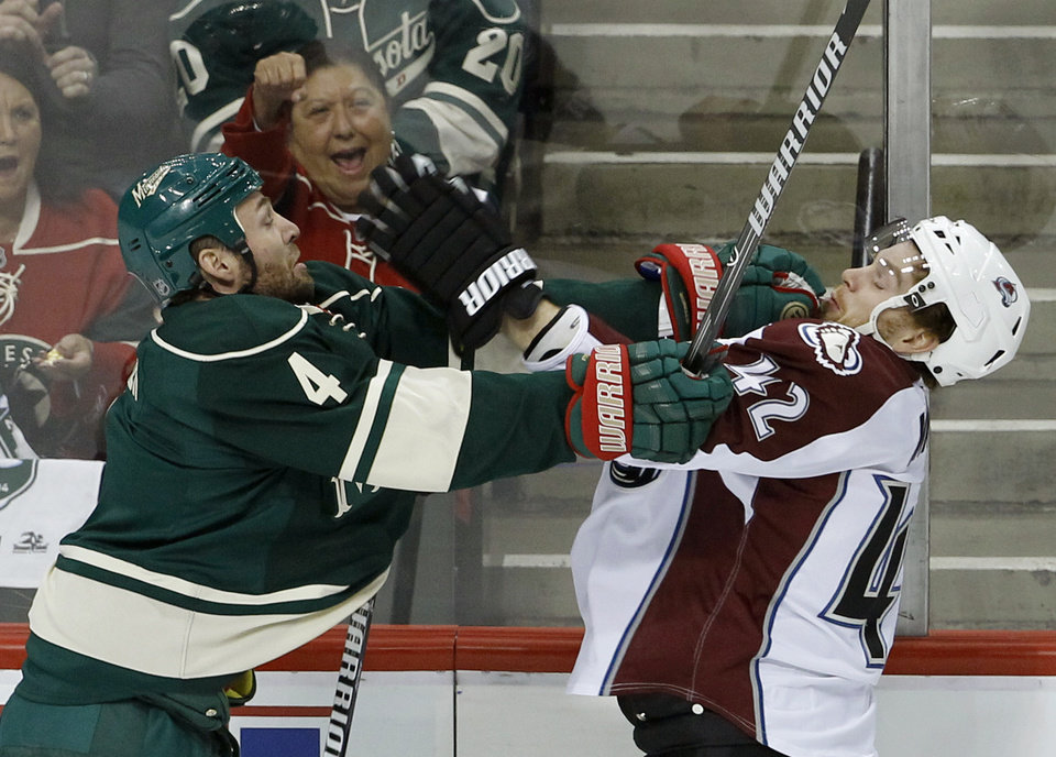 Photo - Minnesota Wild defenseman Clayton Stoner (4) shoves Colorado Avalanche center Brad Malone (42) during the first period of Game 3 of an NHL hockey first-round playoff series in St. Paul, Minn., Monday, April 21, 2014. (AP Photo/Ann Heisenfelt)