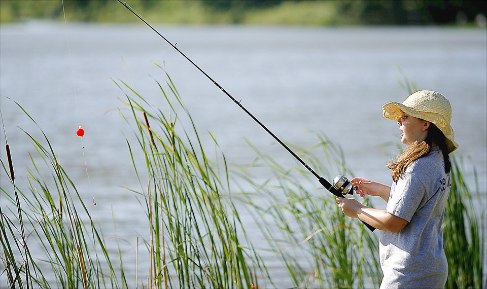 Photo - Madison Green, 10, of Choctaw, reels in her line.