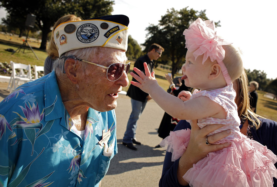 Photo - Pearl Harbor survivor Kenneth Adams, left, leans out as 6-month-old Kalani Parsons, the great-granddaughter of fellow survivor Charles Peters, reaches to touch his medals during the Pearl Harbor 71st Anniversary Memorial Service Friday, Dec. 7, 2012 at Laurel Land Memorial Park in Dallas. (AP Photo/The Dallas Morning News, G.J. McCarthy)  MANDATORY CREDIT; MAGS OUT; TV OUT; INTERNET OUT; AP MEMBERS ONLY