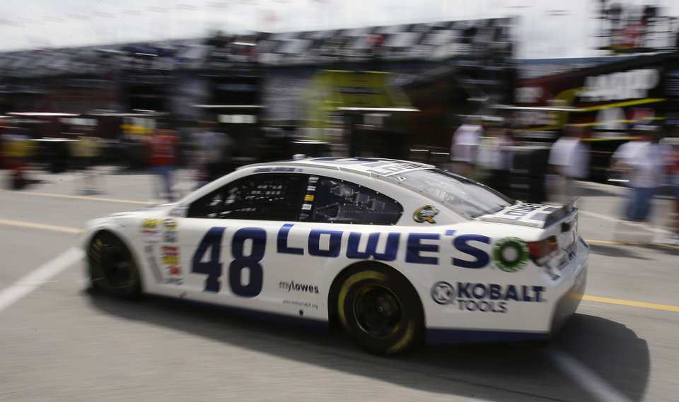 Photo - Jimmie Johnson drives to the track from his garage during practice for the NASCAR Sprint Cup auto race at Daytona International Speedway, Thursday, July 4, 2013, in Daytona Beach, Fla. (AP Photo/John Raoux)