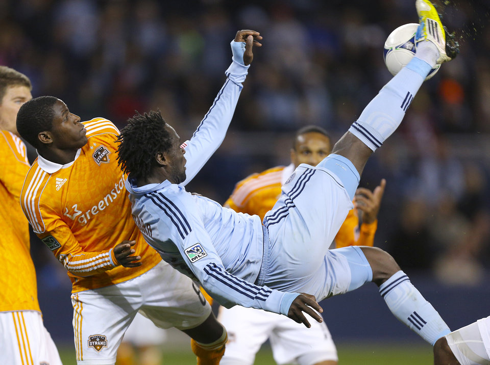 Photo -   Sporting Kansas City's Kei Kamara, front, tries to gain control of the ball against Houston Dynamo's Kofi Sarkodie during the second half of an MLS soccer playoff game Wednesday, Nov. 7, 2012, in Kansas City, Kan. Sporting KC won the game 1-0, but Houston won the series on aggregate, 2-1. (AP Photo/Ed Zurga)