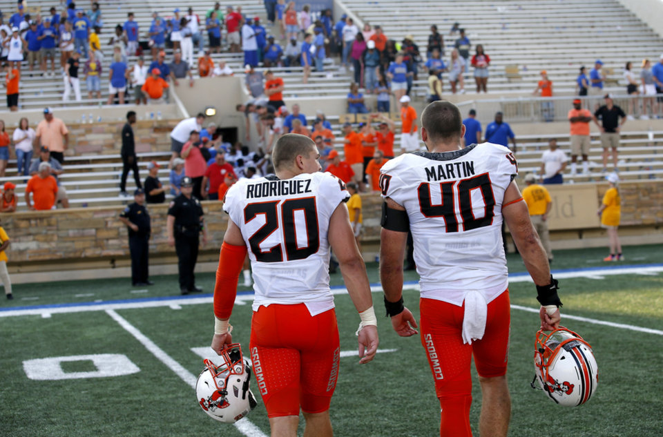 Photo - Oklahoma State's Malcolm Rodriguez (20) and Brock Martin (40) walk off the field together during a college football game between the Oklahoma State University Cowboys (OSU) and the University of Tulsa Golden Hurricane (TU) at H.A. Chapman Stadium in Tulsa, Okla., Saturday, Sept. 14, 2019. [Sarah Phipps/The Oklahoman]