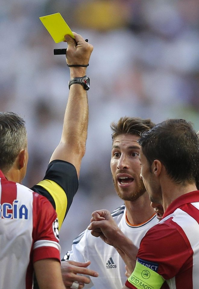 Photo - Real's Sergio Ramos, centre is given a yellow card by referee Bjorn Kuipers,  during the Champions League final soccer match between Atletico de Madrid and Real Madrid, at the Luz stadium, in Lisbon, Portugal, Saturday, May 24, 2014. (AP Photo/Daniel Ochoa de Olza)