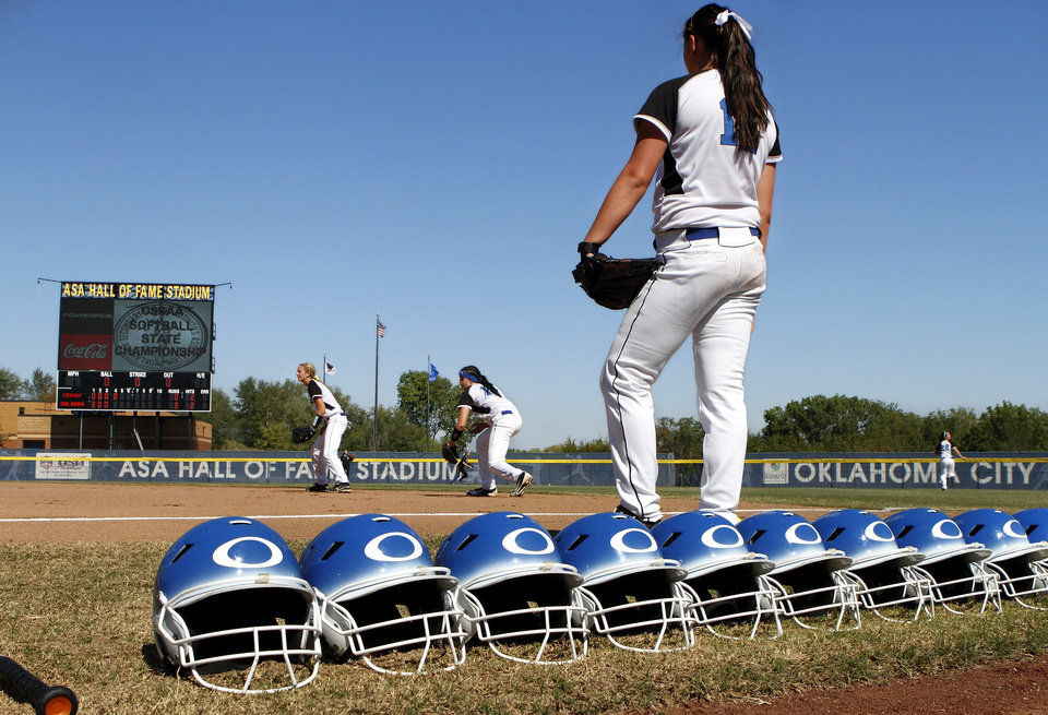 Photo - Batting helmets stretch down the first base line as Oologah players warm up before their game. Class 4A high school championship softball game between Oologah and Piedmont at Hall of Fame Stadium in Oklahoma City on Saturday, Oct. 15, 2012.  Oologah won the game in the bottom of the sixth inning when Baleigh Hamilton scored the winning run on a hit by Alex Edinger, allowing them to claim the victory by virtue of the the run rule, defeating Piedmont,  10-0.    Photo by Jim Beckel, The Oklahoman