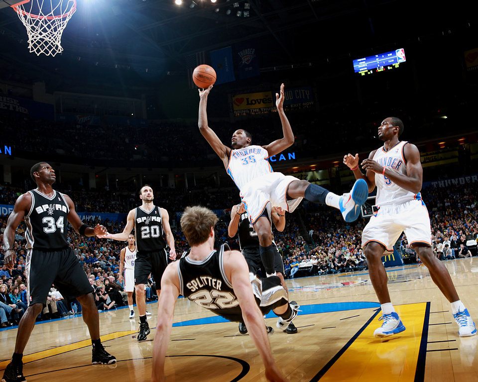 Photo - Oklahoma City's Kevin Durant puts up a shot and draws a foul from San Antonio's Tiago Splitter during their NBA basketball game in downtown Oklahoma City  on Sunday, Nov. 14, 2010.Photo by John Clanton, The Oklahoman