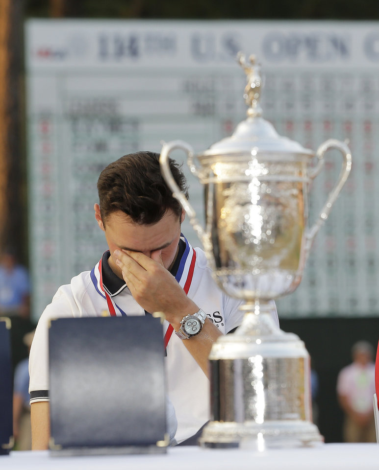 Photo - Martin Kaymer, of Germany, wipes his eyes behind the trophy after wining the U.S. Open golf tournament in Pinehurst, N.C., Sunday, June 15, 2014.  (AP Photo/Eric Gay)