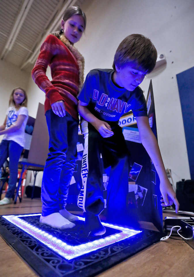 MADISON SCHULZ: Madison and Landon Schulz demonstrate their light up door mat during the Deer Creek Middle School science fair on Thursday, March 14, 2013, in Oklahoma City, Okla. Photo by Chris Landsberger, The Oklahoman
