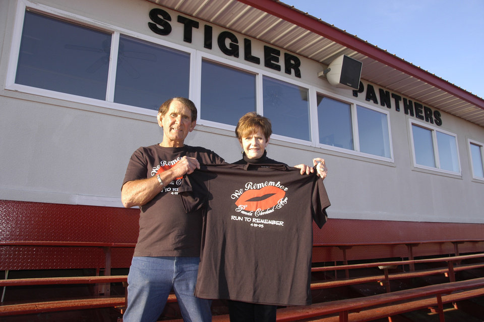 Photo -  Billy and Joyce Cleveland of Stigler hold the shirt that runners from Stigler wear each year in the Oklahoma City Memorial Marathon in memory of their daughter, Pamela Cleveland Argo. PHOTO PROVIDED    Photo provided