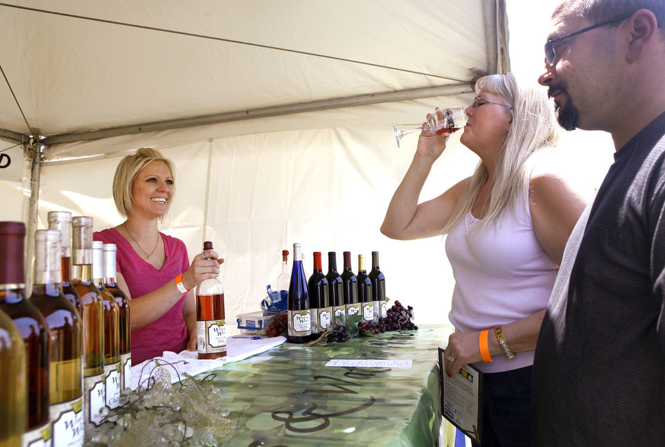 Charity Middleton, left,  offers wine to