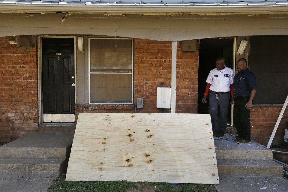 Photo - Workers repair a neighbor's front door, at right, blown off during a raid when FBI agents on Wednesday rescued Frank Arthur Janssen, of Wake Forest, N.C., from an apartment, at left, in a housing complex in Atlanta, Thursday, April 10, 2014. John Strong, FBI special agent in charge in North Carolina, said Janssen's kidnapping was related to his daughter's prosecution of North Carolina prisoner Kelvin Melton, who is serving a life sentence for his 2012 conviction for being a habitual felon.  (AP Photo/David Goldman)