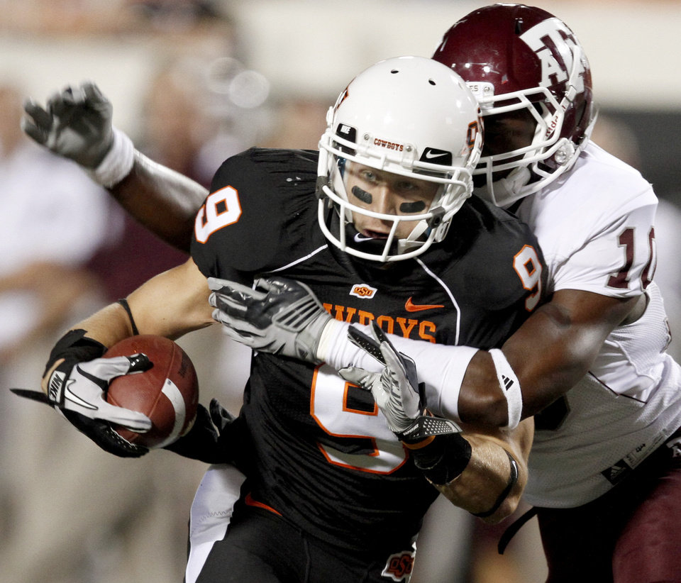 Photo - OSU's Bo Bowling tries to get past Texas A&M's Sean Porter during the college football game between Texas A&M University and Oklahoma State University (OSU) at Boone Pickens Stadium in Stillwater, Okla., Thursday, Sept. 30, 2010. Photo by Bryan Terry, The Oklahoman