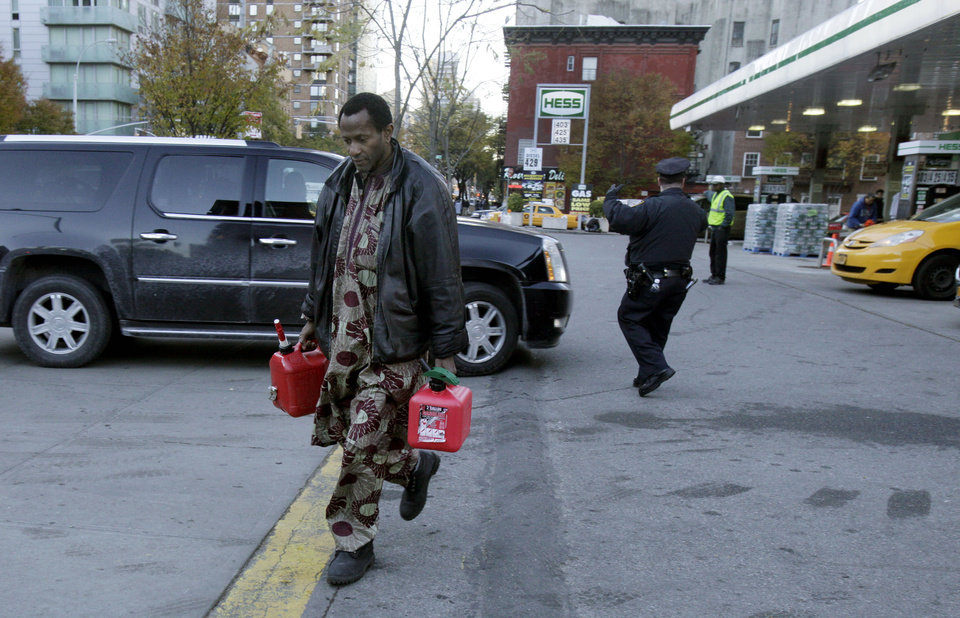 Photo -   A man carries two filled gas cans at a gasoline station, in New York, Friday, Nov. 9, 2012. A new gasoline rationing plan that lets motorists fill up every other day went into effect in New York on Friday morning. Police were at gas stations to enforce the new system in New York City and on Long Island. (AP Photo/Richard Drew)