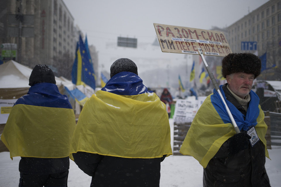 Photo - Pro-European Union activists wearing Ukrainian National flags walk through the Independence Square in KIev, Ukraine, Monday, Dec. 9, 2013.  The poster on right reads