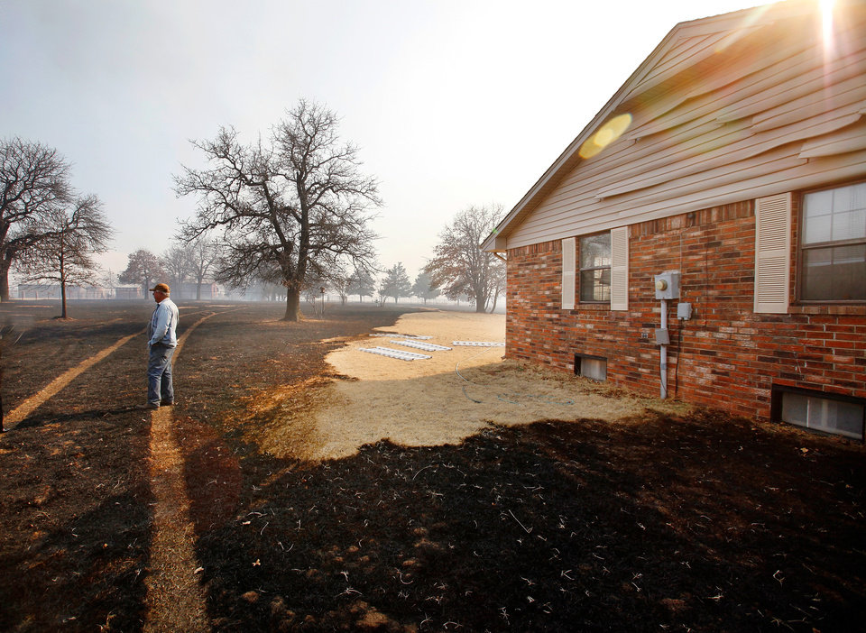 Photo - Tom Simon stands in his charred yard on NE 23 surveying the damage the wild fire left behind Friday, March 11, 2011. Photo by Jim Beckel, The Oklahoman
