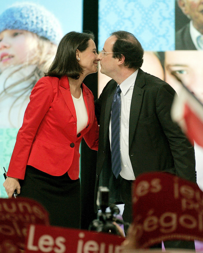 FILE - In this March 29, 2007 file photo, Socialist French presidential candidate Segolene Royal, left, kisses her partner Secretary-General of the Socialist Party Francois Hollande during a meeting in Limoges, central France. Royal, French President Francois Hollande's former partner, has been named Wednesday April, 2, 2014 as Minister of Environment and Energy. (AP Photo/Francois Mori, File)